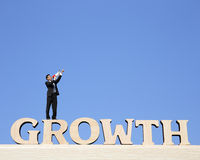 Growth business concept. Business man stand on Growth text word and using megaphone shouting with blue sky background Royalty Free Stock Photo
