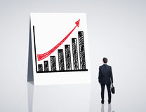 Growth chart. Man looking at poster with growth chart Royalty Free Stock Photo