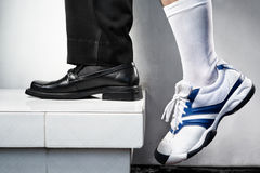 Growth concept. From school to business world, one leg step from below with leg using casual shoe and the other leg using business attire. Legs of one person Royalty Free Stock Photos
