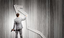 Growth concept. Rear view of businessman fixing wooden graph arrow with drill Stock Image