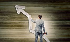 Growth concept. Rear view of businessman fixing wooden graph arrow with drill Royalty Free Stock Photos