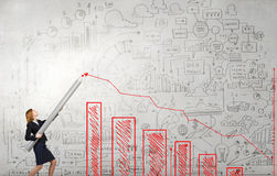 Growth concept. Young businesswoman drawing growing graph with huge pencil Stock Image