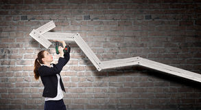 Growth concept. Young businesswoman fixing increasing arrow with drill Royalty Free Stock Photos