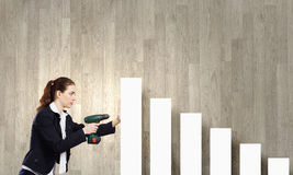 Growth concept. Young businesswoman fixing increasing arrow with drill Stock Photography
