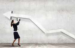 Growth concept. Young businesswoman fixing increasing arrow with drill Royalty Free Stock Image