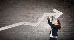 Growth concept. Young businesswoman fixing increasing arrow with drill Royalty Free Stock Images