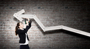 Growth concept. Young businesswoman fixing increasing arrow with drill Royalty Free Stock Photo