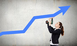 Growth concept. Young businesswoman fixing increasing arrow with drill Stock Image