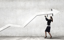 Growth concept. Young businesswoman fixing increasing arrow with drill Stock Photo
