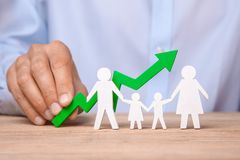 Growth of the family budget. Man holds green arrow up against the background of family. Of father, mother, daughter and son stock photos