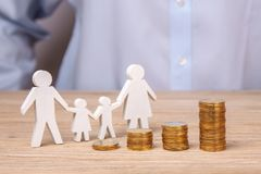 Growth of the family budget. Man holds family from his father, mother, daughter and son against the background of stack of coins.  stock photo