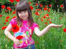 Growth and flowering. Girl with brown eyes and dark hairs on the field of red poppies. Opened palm Royalty Free Stock Photography