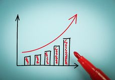 Growth graph. Is on blue paper with a red marker aside Royalty Free Stock Photo