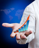 Growth graph on hand. Business man holding growth graph with world map background Royalty Free Stock Photography