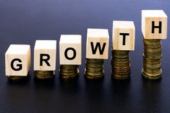 Growth. Word on Wood Block on Top of Coins Stack With Black Background Stock Photo