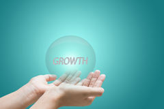 Growth. Hands holding bubble containing text 'growth' in white uppercase letters, green background royalty free stock image