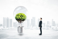 Growth and idea concept. Thoughtful businessman looking at absract lamp with tree inside on city background. 3D Rendering. Growth and idea concept vector illustration