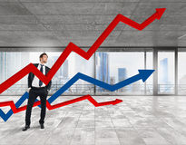 Growth in profits. Business man in office with arrows upwards Royalty Free Stock Photography