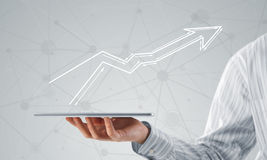 Growth and progress in business. Close view of businessman holding tablet presenting growth concept Stock Images