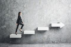 Growth and promotion concept. Side view of young businesswoman climbing abstract white arrow ladder on concrete background. Growth and promotion concept stock image