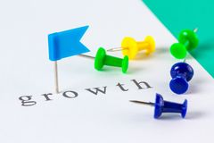 Growth push pin. Flag push pin on paper at growth word Stock Photo
