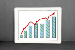 Growth red arrow and chart on tablet  with concrete wall Stock Photo