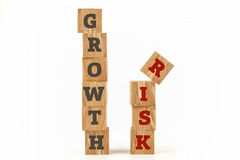 Growth and Risk word written on cube shape. Growth and Risk word written on cube shape wooden surface isolated on white background Stock Images