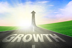 Growth road to success. Success road with increase arrow sign and writing of GROWTH on it at green field Stock Photography