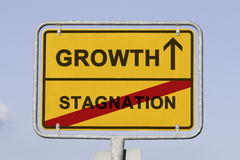 Growth and stagnation. Blue sky behind a yellow city limit or place name sign informing with an arrow that you are on the way to growth and leaving stagnation Stock Photo