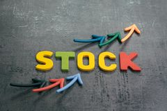 Growth in stock market rising price concept, arrows pointing up as price chart with colorful letters building word STOCK on loft. Cement dark chalkboard, equity stock photography
