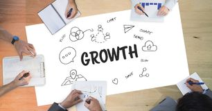 Growth text by icons and business people on table. Digital composite of Growth text by icons and business people on table Royalty Free Stock Photos