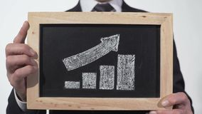 Growth up arrow graphic drawn on blackboard in businessman hands, company report. Stock footage stock video