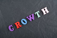 Growth word on black board background composed from colorful abc alphabet block wooden letters, copy space for ad text Royalty Free Stock Photos