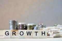Growth Word Written In Wooden Cube on wood table with money stack up as graphs in background stock images