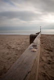 Groyne. A beach groyne extending into the distance off centre, with a few shells on the woodwork, on a sandy beach with the sea in the distance Stock Image