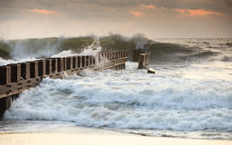 Groyne Bashed by Ocean Waves North Carolina. This groyne in Buxton, NC takes a bashing from angry ocean waves.  This hydraulic structure  limits the movement of Royalty Free Stock Images
