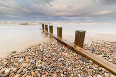 Groyne or groin on pebble beach Stock Image