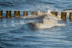 Groynes in the surge of baltic sea. A row of groynes in the surge of waves of the baltic sea, Germany, Europe stock photos