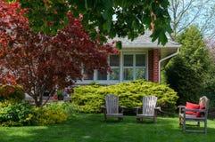 Gräsmattastolar framme av ett hus Fotografering för Bildbyråer