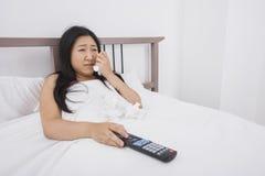 Gråt för ung kvinna, medan hålla ögonen på TV i säng Arkivfoto
