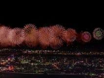 Gruß über der Stadt die Großstadt Festlicher Gruß im nächtlichen Himmel Explosionen von Feuerwerken stockbilder