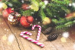 Gruß-Karte für die Weihnachtsfeiertage Fichtenzweig-Kegel-Süßigkeit Cane Christmas spielt hölzernen Hintergrund Weihnachtshinterg Lizenzfreie Stockfotos