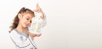 Gruß-Karte: Glückliches junges moslemisches Mädchen, das mit Laterne herein spielt stockfotografie