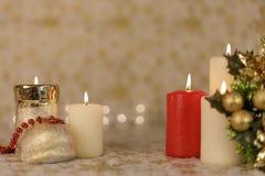 Gruß-Weihnachtskarte mit brennenden Kerzen und roter Dekoration Stockfotografie