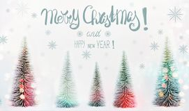 Grußkarte der frohen Weihnachten und des guten Rutsch ins Neue Jahr mit Textbeschriftung, Tannenbaumwald und Sonnenschein bokeh lizenzfreie stockfotografie