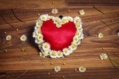 Grußkarte des Herzens mit Gänseblümchen und Schmetterlingen auf hölzernem Brett Lizenzfreie Stockfotos