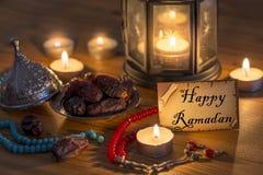 Grußkarte, die glückliches Ramadan mit Daten, Rosenbeet, Kerzen auf Holztisch schreibt lizenzfreie stockfotografie
