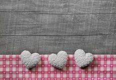 Grußkarte: drei weiß und rosa überprüfte Herzen auf hölzernem gre Lizenzfreie Stockfotos