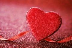 Grußkarte am Heilig-Valentinstag mit rotem Herzen und Band auf hellem Hintergrund Lizenzfreies Stockfoto