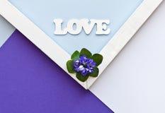 Grußkarte mit blauen Blumen und Liebe stellen auf dem bunten Papierhintergrund dar Geometrische Muster des Blumenebenenlage-Minim Stockbilder